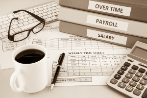 Human resources documents: payroll salary and employee time sheets place on office table with cup of coffee and calculator sepia tone